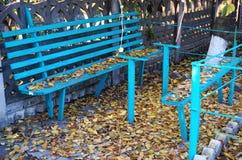 老蓝色长木凳和下落的秋叶 免版税库存图片