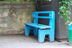 老蓝色长木凳和下落的秋叶 免版税库存照片