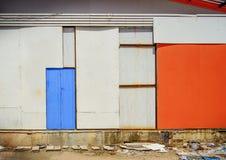 老蓝色门关闭了有橙色胶合板背景 库存照片