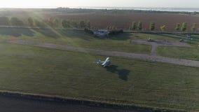 老螺旋桨推进式飞机在领域中的绿草登陆在阳光下反对蓝天入在寄生虫视图的太阳天气 影视素材