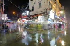 老街道夜视域在雨、步行者和游人的 图库摄影