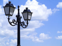 老街道装饰了路灯柱反对多云蓝天 库存照片