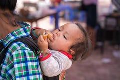 老街,越南- 2017年9月7日:她的母亲后面的少数族裔孩子在Y Ty,棒Xat区的地方市场上 库存图片