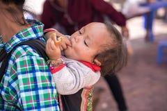 老街,越南- 2017年9月7日:她的母亲后面的少数族裔孩子在Y Ty,棒Xat区的地方市场上 免版税库存图片