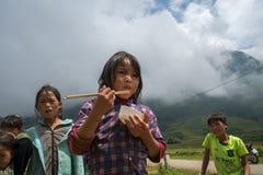 老街,越南- 2017年9月7日:少数族裔孩子吃与她的家庭的午餐在收获季节的米领域在Sapa 免版税库存照片