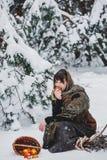 老衣裳的一个少妇坐与草丛和一个篮子用苹果在雪在冬天森林里 库存照片