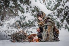 老衣裳的一个少妇坐与草丛和一个篮子用苹果在雪在冬天森林里 免版税库存图片