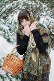 老衣裳的一个少妇站立与一个篮子和草丛在雪在冬天森林里 免版税库存照片
