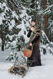 老衣裳的一个少妇站立与一个篮子和草丛在雪在冬天森林里 免版税库存图片