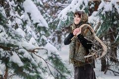 老衣裳的一个少妇站立与在一个冬天森林字符的草丛从童话 免版税库存图片