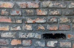 老被佩带的红砖墙壁和黑砖关闭  Grunge纹理 免版税库存图片