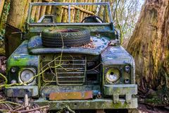 老被击毁的吉普在森林里,被放弃的车,徒步旅行队装饰 库存照片