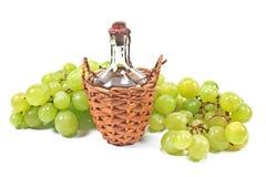 老被密封的瓶酒和白葡萄 免版税图库摄影