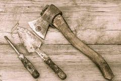老被弄脏的轴、修平刀和螺丝刀老木表面上 库存图片