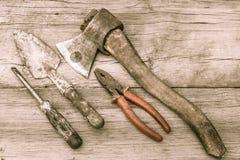 老被弄脏的轴、钳子、修平刀和螺丝刀在老木su 免版税库存照片