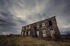 老被放弃的农厂房子在多云天空下 库存图片
