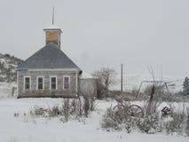 老被放弃的学校房子在麦考尔,爱达荷附近的冬天 库存图片