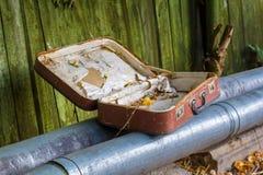 老被放弃的手提箱在管子说谎 免版税库存照片