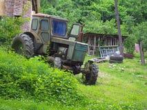 老被放弃的拖拉机在离开的农村农庄站立 免版税图库摄影