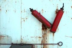 老被放弃的消防盾 两在盾的生锈的灭火器 老,被放弃的火设备 图库摄影