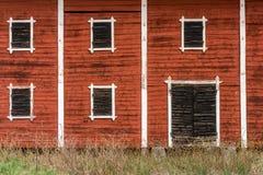 老被放弃的腐朽的红色谷仓外部有闭合的木窗口的关闭 库存图片