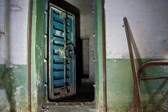 老被放弃的苏联防空洞的蓝色生锈的密封门 免版税库存图片