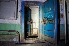 老被放弃的苏联防空洞的蓝色生锈的密封门 免版税库存照片