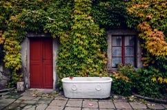 老被放弃的葡萄酒减速火箭的白色浴缸 免版税图库摄影