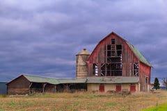 老被放弃的谷仓与黑暗的多云天 免版税库存照片