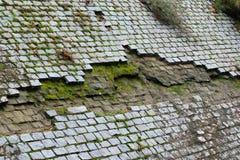 老被铺的墙壁,生苔肮脏和缺掉鹅卵石 库存照片