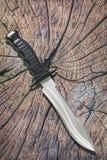 老被风化的破裂的树桩土气顶面上的作战作战狩猎生存Sawback猎刀集合 免版税库存图片