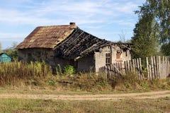 老被破坏的农舍在路附近 免版税库存图片