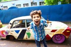 老被绘的减速火箭的汽车背景的男孩 免版税库存图片