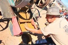 老西部:古色古香的捣碎机的现代金探油矿者 库存图片