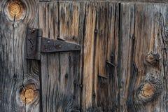 老谷仓木板条门和生锈的铰链 库存图片