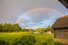 老谷仓房子和双重彩虹 苹果覆盖花横向草甸本质星期日结构树 库存照片
