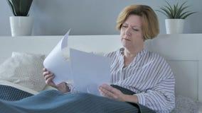 老资深妇女读书文件在床上,文书工作 股票录像