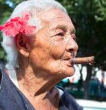 老起皱纹的妇女抽烟的雪茄 免版税库存图片