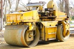 老路摊铺机在一条滚动的土路站立在城市 免版税图库摄影