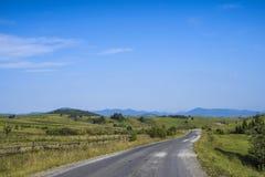 老路通过在山的一个领域在一个晴朗的下午 图库摄影