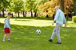 老踢橄榄球的人和男孩在夏天公园 库存照片