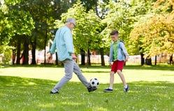 老踢橄榄球的人和男孩在夏天公园 免版税库存图片