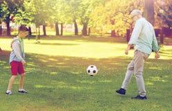 老踢橄榄球的人和男孩在夏天公园 免版税图库摄影