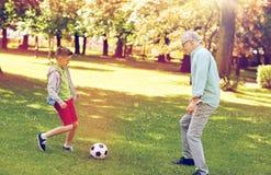 老踢橄榄球的人和男孩在夏天公园 免版税库存照片