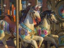 老转盘五颜六色的马在金黄晚上点燃 免版税库存图片