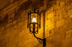 老轻垂悬在中世纪街道堡垒墙壁上在晚上 库存图片