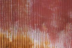 老退色的和生锈的红色被绘的山脊金属表面或背景 库存图片