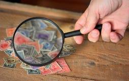 老邮票和放大镜 免版税库存图片