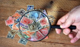老邮票和放大镜 图库摄影