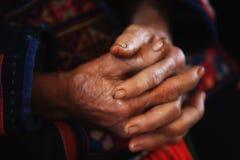老部族妇女用被扣紧的皱痕手 库存照片
